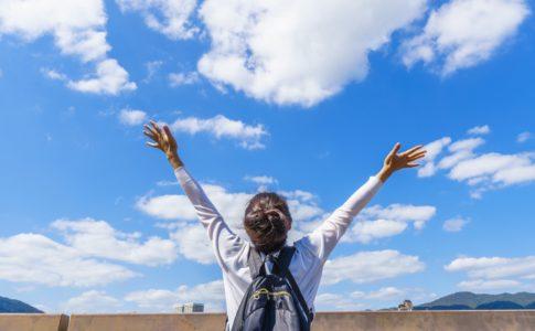 空に向けて両手を広げている女性