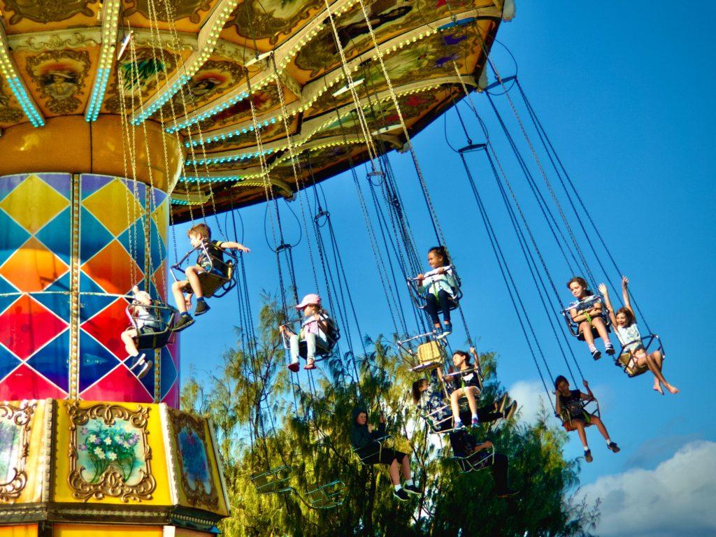 遊園地の乗り物に乗る子供達
